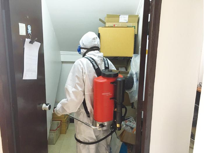 専用の服を着て除菌作業を行う